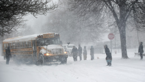Community members get together to help get a school bus unstuck near Central Avenue and Grotto Street in St. Paul during a snow storm in St. Paul on Monday, Jan. 22, 2018. Eventually a tow truck was called to help pull the school bus out of the snow.  (John Autey / Pioneer Press)