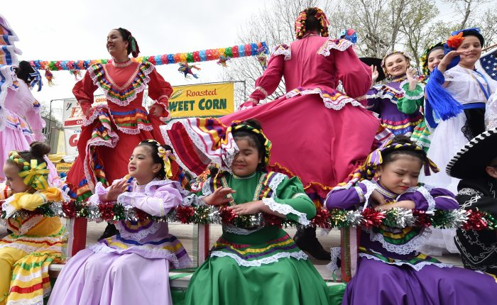 A girl gets dress to the face as dancer behind her twirl and spin on a float at the St. Paul West Side's Cinco de Mayo festival along Cesar Chavez Street on Saturday, May 5, 2018. (John Autey / Pioneer Press)